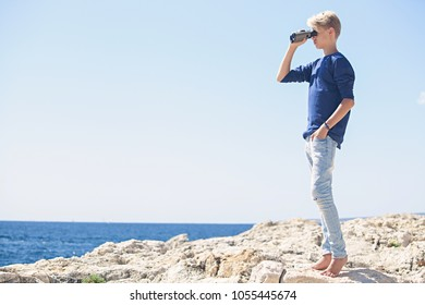 Teenager male on sea cliff rock using binoculars contemplating the blue sea on sunny holiday, outdoors. Young man looking through binoculars, adventure discovery travel recreation leisure lifestyle.