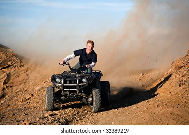 teenager male riding a quad / four wheeler in rural Wyoming