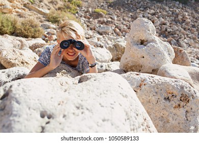 Teenager male in rocky terrain laying hiding looking through binoculars in textured stones, sunny outdoors. Young man using binoculars observing, eyes vision seeing sight leisure recreation lifestyle.