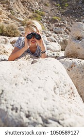 Teenager male in textured rocky terrain laying hiding looking through binoculars in sunny outdoors. Young man using binoculars observing, eyes vision seeing sight, leisure recreation lifestyle.