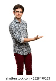 Teenager man with flower shirt and glasses presenting an idea while looking smiling towards over isolated white background