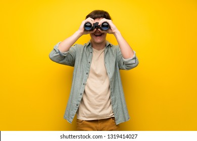 Teenager man over yellow wall and looking in the distance with binoculars
