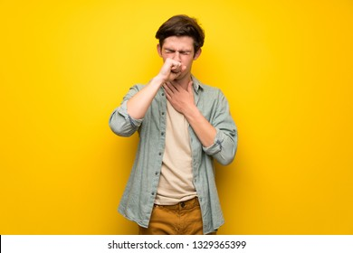 Teenager man over yellow wall is suffering with cough and feeling bad