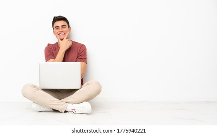 Teenager man sitting on the flor with his laptop smiling