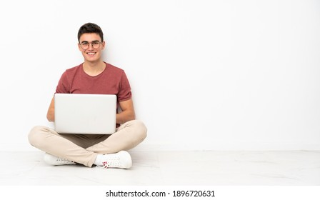 Teenager man sitting on the flor with his laptop
