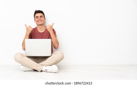 Teenager man sitting on the flor with his laptop with thumbs up gesture and smiling