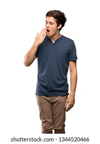 Teenager man yawning and covering wide open mouth with hand over isolated white background