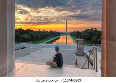 Teenager meets sunrise at the Lincoln Memorial in morning summertime. Washington Monument Sunrise from Lincoln Memorial, Washington DC, USA.