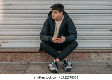 teenager with mobile phone sitting on the street