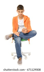 Teenager with mobile phone sitting on chair against white background