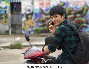 Teenager with mobile telephone sitting on motorbike