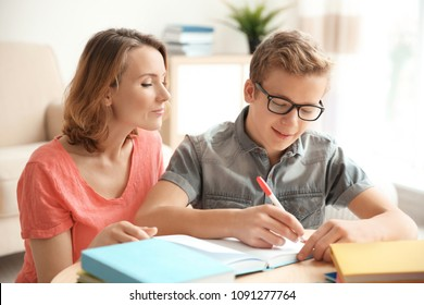 Teenager with mother doing homework at home