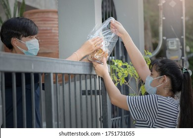 Teenager neigbor are sharing the food and snack over the fence. Both of them wearing facemask to prevent themselve from COVID-19 spreading. New normal, social distancing concept.
