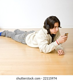 teenager on floor listening to music with headphones