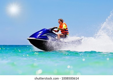 Teenager on jet ski. Teen age boy skiing on water scooter. Young man on personal watercraft in tropical sea. Active summer vacation for school child. Sport and ocean activity on beach holiday