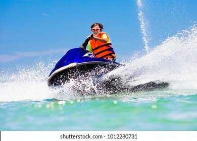 Teenager on jet ski. Teen age boy skiing on water scooter. Young man on personal watercraft in tropical sea. Active summer vacation for school child. Sport and ocean activity on beach holiday.