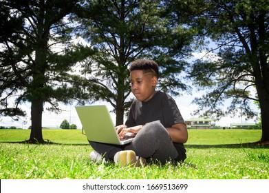 Teenager on Laptop computer in park located near Atlanta, GA