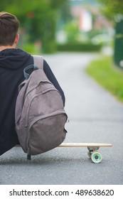 Teenager on a longboard casually sitting on his longboard on a suburban street.