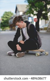 Teenager on longboard looking down.
