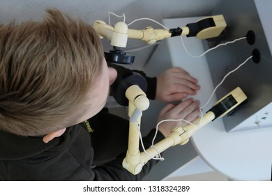 A teenager on a physiotherapy procedure warms up the nose on the UHF apparatus in the hospital. Treatment of rhinitis with ultra high frequency manipulators. View from above.