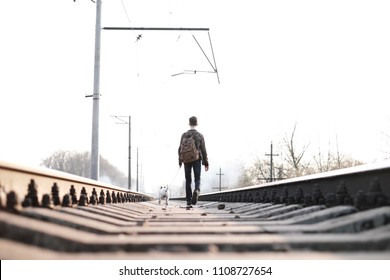 Teenager on railway walking with small white dog. Freedom and loneliness concept