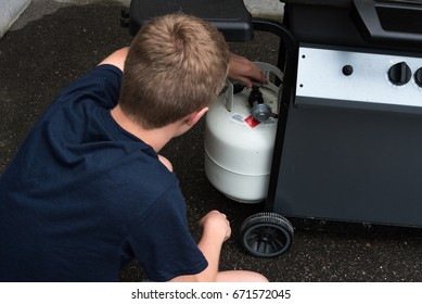 Teenager opening a propane tank for a barbecue, Canada.