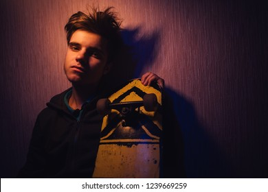 teenager in the orange-blue light with a skateboard