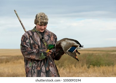 A teenager out Duck hunting with a Mallard Duck