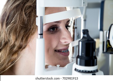 Teenager patient at optometrist clinic doing biomicroscopy with slit lamp procedure.