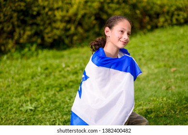 Teenager patriot jewish girl sitting with the flag of Israel wrapped around her. Memorial day-Yom Hazikaron and Yom Ha'atzmaut concept.