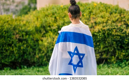 Teenager patriot jewish girl standing with the flag of Israel wrapped around her. Memorial day-Yom Hazikaron and Yom Ha'atzmaut concept.