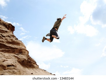 Teenager performs freerunning jump on sand hill
