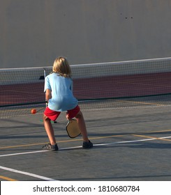 Teenager playing a fast game pickle ball, a sport many associate with a slow moving seniors.