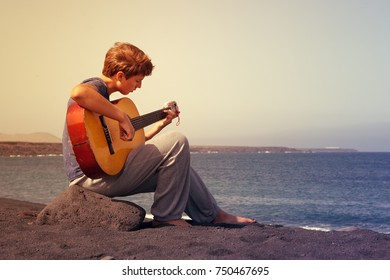 Teenager playing on guitar in the ocean coast.