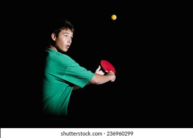 Teenager playing ping-pong on black background