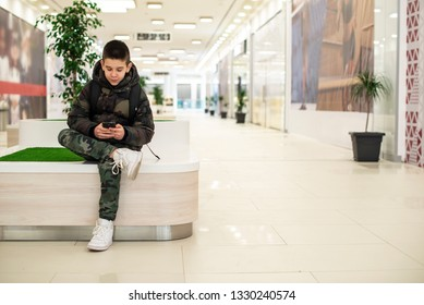 Teenager playing with smartphone in modern commercial center. Bench and flower in a pot. Modern building interior. Technology and communication concept with child in contemporary building interior.