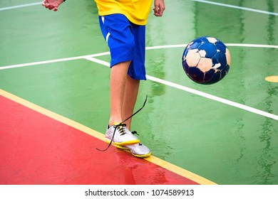 Teenager playing soccer on court.