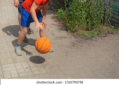 Teenager plays basketball with his father. Closeup view with no faces. Boy and man bounce the ball on a backyard. Sport fans at sunny summer day