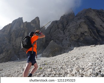 Teenager pointing his stick at tall rockface, partly covered by a cloud, anticipating the future