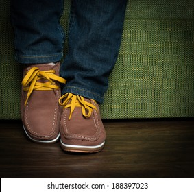 Teenager posing her jeans and shoes, sitting on a green sofa.
