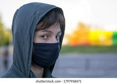 Teenager in einer Schutzmaske. Coronavirus COVID-19 Pandemie. Blick in die Kamera. Seitenansicht. Leerzeichen kopieren