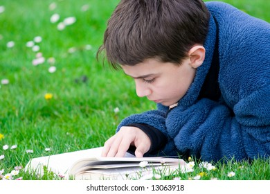 Teenager reading in grass