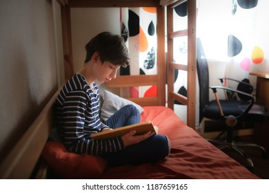 teenager reads a book on a bed in his room, darkness, a real interior.