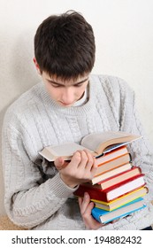 Teenager reads a Books on the Sofa at the Home