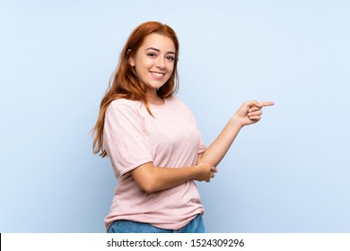 Teenager redhead girl over isolated blue background pointing finger to the side