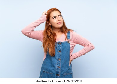 Teenager redhead girl with overalls over isolated blue background having doubts and with confuse face expression