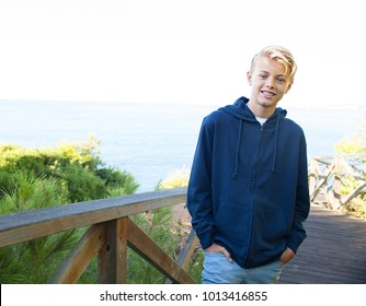 Teenager relaxing on sunny holiday park by the sea, smiling joyful contemplating nature outdoors. Young tourist man walking on wooden deck visiting destination beach, healthy travel active lifestyle.