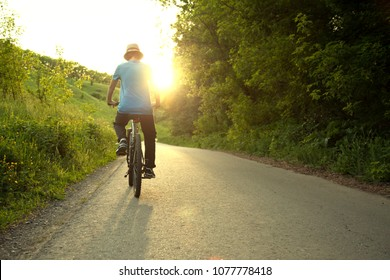 teenager riding a bicycle on the road summer sunlit, bike ride