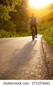 Teenager riding a bike on the road summer sunlit, bicycle ride outdoors