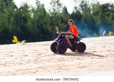 Teenager riding quad bike on tropical beach. Active teen age boy on quadricycle. All-terrain vehicle ride. Motor cross sports on ocean sand dune. Off road race at sea shore. Summer vacation activity.